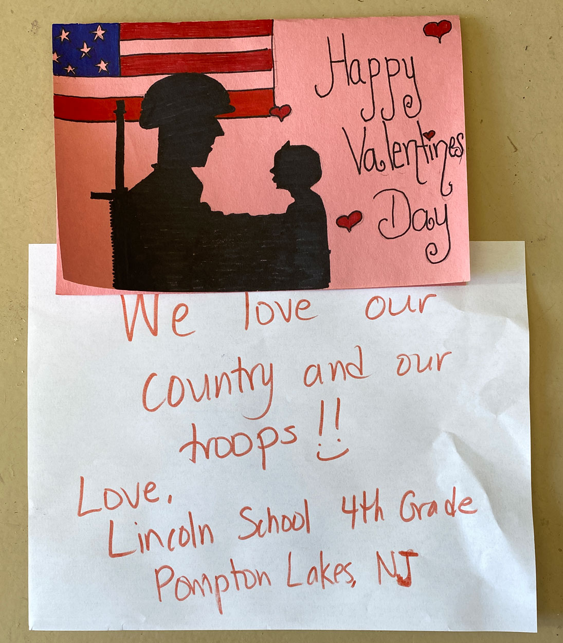 "New Jersey, February 7, 2021 –     The 4th Grade students at  Lincoln School, Pompton Lakes, New Jersey say ""We love our country and our troops !!:)""  and cleverly converted the SOT soldier&child logo into their Valentine Day card art.   Good job!"
