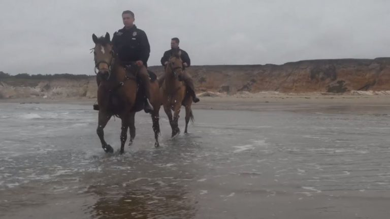 Air Force Staff Sgt. Zechariah Landa and Senior Airman Michael Terrazas trot along the beach on the unit's working horses.