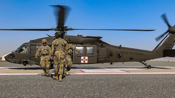 U.S. Army Soldiers assigned to the 2-211th General Support Aviation Battalion, Minnesota Army National Guard, and the 155th Armored Brigade Combat Team, Mississippi Army National Guard, pull a patient from a UH-60L Black Hawk helicopter during an aeromedical evacuation rehearsal at Camp Buehring, Kuwait, Dec. 11, 2018. (Photo by Sgt. Emily Finn)