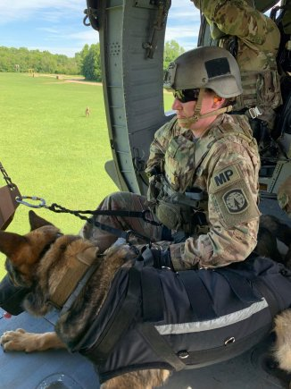 Sergeant Megan Hurley and Military Working Dog Bill from the 510th Military Police Detachment (MWD), 716th Military Police Battalion, 101st Sustainment Brigade, prepare to fast rope out of a UH-60 Blackhawk Helicopter during pre-deployment training. From providing unique patrol, explosives and narcotic detection capabilities through law enforcement on Fort Campbell, Kentucky to deploying into combat zones such as Iraq and Afghanistan, the 510th MP DET is staying busy. (U.S. Army photo by: 1st Lt. M. Austin Giles, 510th Military Police Detachment (MWD), 716th Military Police Battalion) (Photo Credit: Courtesy)