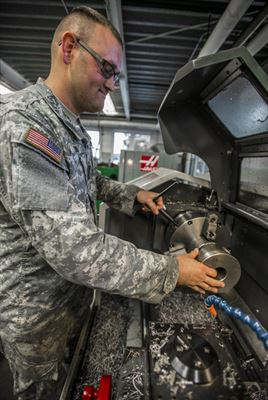Illinois Army National Guard Sgt. Wesley Todd, of La Porte, Indiana, places his invention that's used to remove the muzzle break from the light towed howitzer, onto a lathe at the Combined Support Maintenance Shop in North Riverside, Illinois, Sept. 21, 2016. Todd device improves soldiers' safety and equipment longevity while working on the light towed howitzer. Illinois Army National Guard photo by Staff Sgt. Robert R. Adams