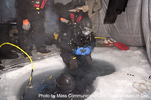 Beaufort Sea, March 10, 2018 - Navy Diver 2nd Class Christopher Corley, assigned to Underwater Construction Team (UCT) 1, prepares to dive into a water hole during a mock torpedo recovery exercise in support of Ice Exercise (ICEX) 2018.  During ICEX 2018, the Seawolf-class fast attack submarine USS Connecticut (SSN 22) from Bangor, Washington, the Los Angeles-class fast attack submarine USS Hartford (SSN 768) from Groton, Connecticut, and the Royal Navy Trafalgar-class submarine HMS Trenchant (S91) will conduct multiple arctic transits, a North Pole surfacing, scientific data collection and other training evolutions during their time in the region.