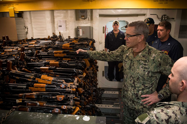 MANAMA, Bahrain, October  24, 2018 - Vice Adm. Scott Stearney, commander of U.S. Naval Forces Central Command, U.S. 5th Fleet and Combined Maritime Forces, looks at a cache of over 2,500 AK-47 automatic rifles seized during maritime security operations aboard the guided-missile destroyer USS Jason Dunham (DDG 109).