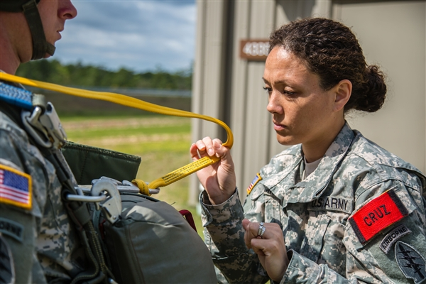Army 1st Sgt. Sandrea Cruz, right, conducts a jumpmaster personnel inspection on a soldier, preparing him for a static-line parachute jump from an aircraft. Cruz leads more than 150 soldiers as the first sergeant for the 7th Special Forces Group's (Airborne) Sustainment and Distribution Company. U.S. Army photo by Staff Sgt. Bryan Henson